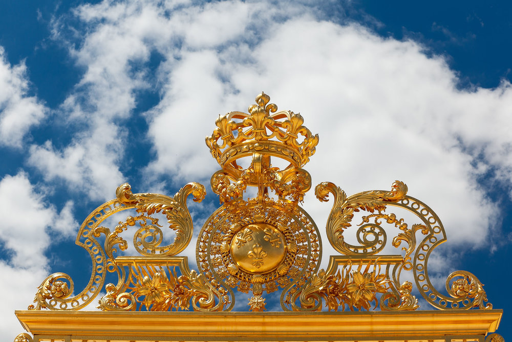 A detail, on the top of the visitor entrance gate, at the    glorious Palace of Versailles    photographed from a    low viewpoint   ; with a    polarizing filter   ; and processed with    added saturation    for    extra drama   .