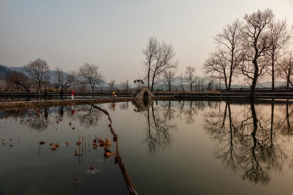 Trees and people reflected in a  pool of water  near an  entrance to the village of Hongcun  in  Anhui Province, China .