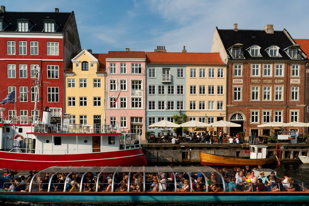 An incredibly colorful scene as a    boat of tourists    sail along the canal at    Nyhavn    in    Copenhagen   .
