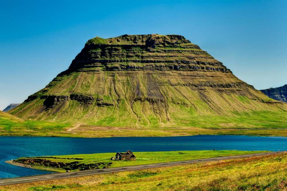 The remains of an old stone dwelling by a fjord, with a mountain towering above and the nation's  Highway One  in the foreground, showcase the history and geography awaiting the intrepid visitor to  Iceland .