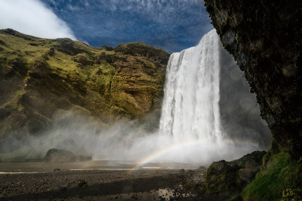 A  rainbow  appears at the bottom of the  magnificient Skógafoss waterfall  in  southern Iceland .