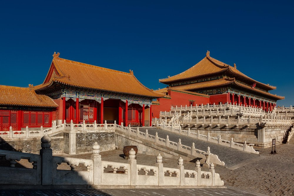 Red walls and orange tiled roofs against a deep blue sky on a  spectacular winter's day  in the  Forbidden City  in  Beijing, China .