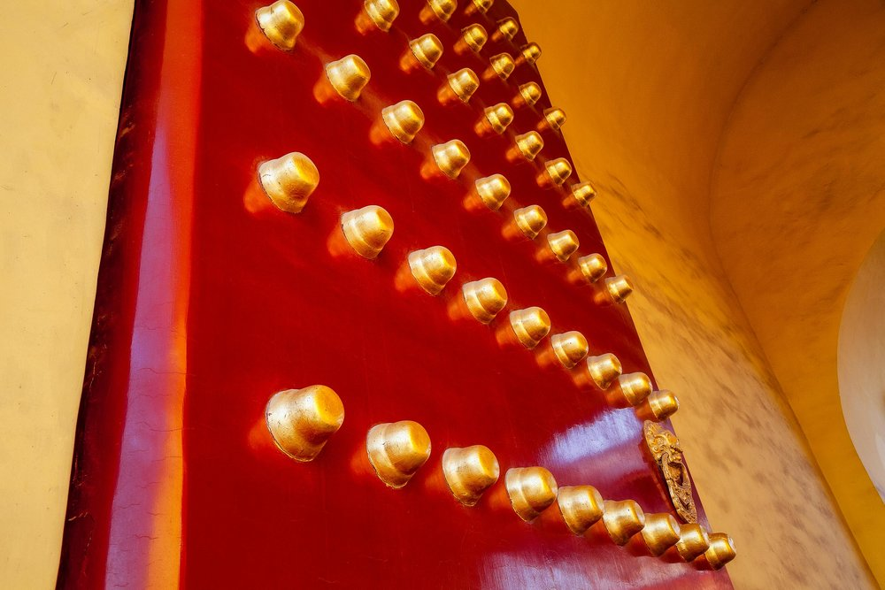 A massive  red door  adorned with  big, brass studs  in the grounds of the  Forbidden City  in  Beijing, China .