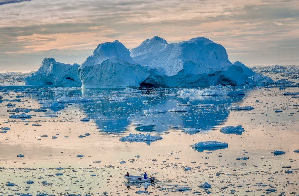 Two fisherman  head out,  under the midnight sun , into the wilds of the spectacular  Ilulissat Icefjord  in  Ilulissat, Greenland .