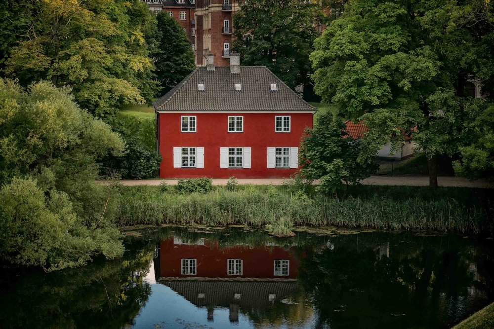A vibrant    red house    by a canal photographed from    Kastellet Fort    in    Copenhagen, Denmark   .