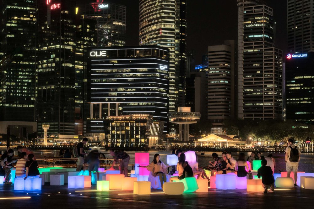 Lots of  beautiful light cubes  by the water outside of the  Marina Bay Sands  shopping complex at night in  Singapore .