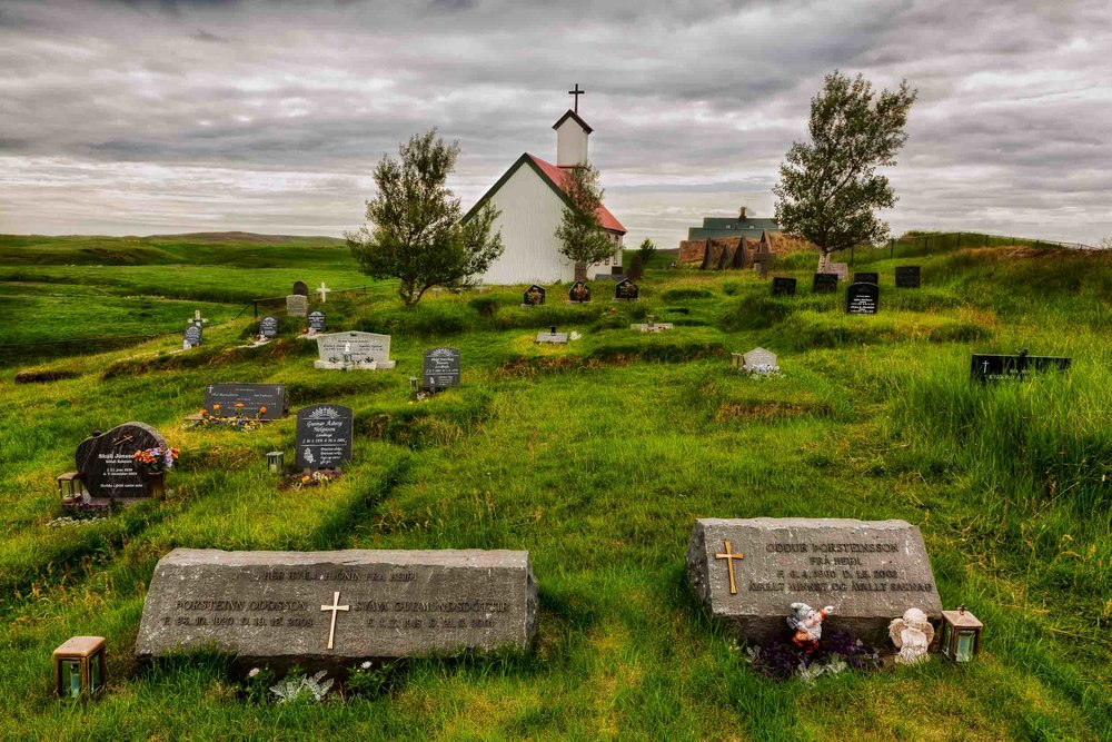 A  graveyard  in lush fields behind a  church  in rural  Iceland .