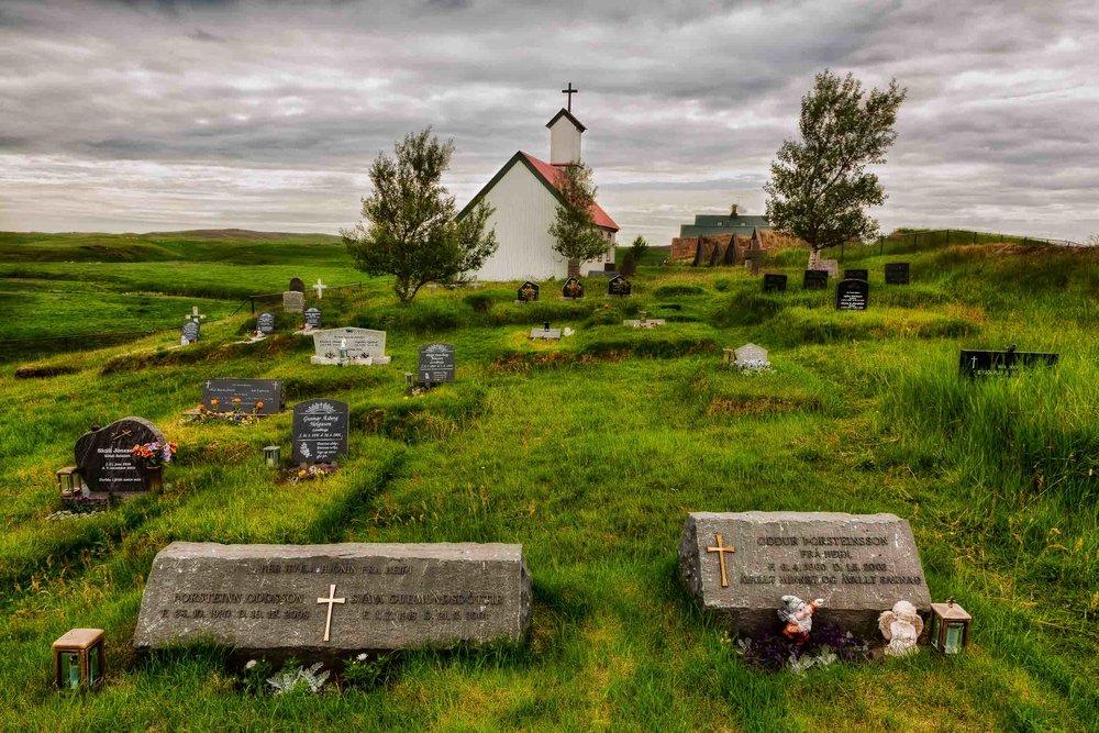A  graveyard  in lush fields behind a  church  in rural  Iceland .