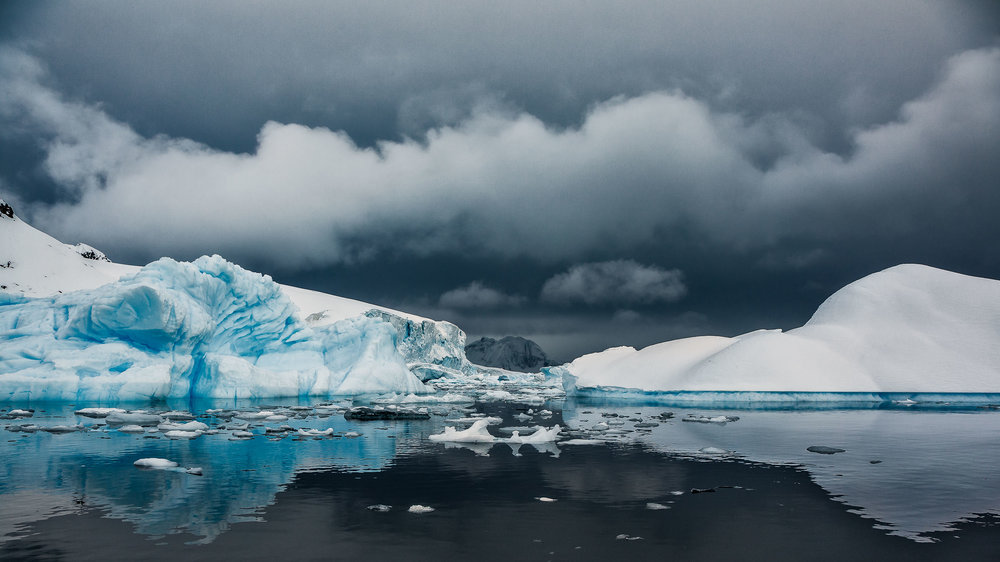 A    dramatic sky and calm waters    frame masses of ice and snow off    Cuverville Island, Antarctica   .