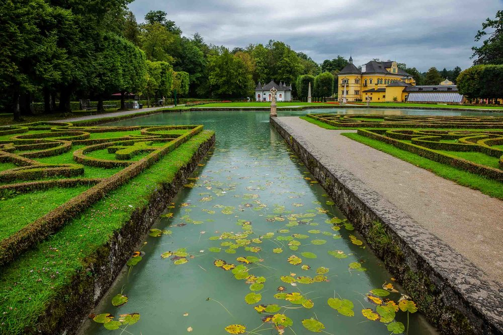 Whatever the weather  Salzburg  is a beautiful destination and a wonderful place to explore on foot. This photo showcases a pool in a  beautifully designed garden  where trees and the colors  green and yellow dominate .