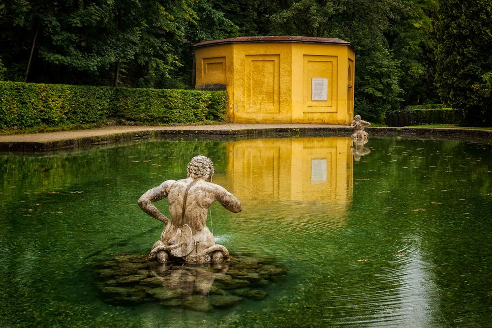 A bright  yellow building  and its  reflection , between two statues in a pond, produce a serene scene in a lovely park setting in  Salzburg, Austria .