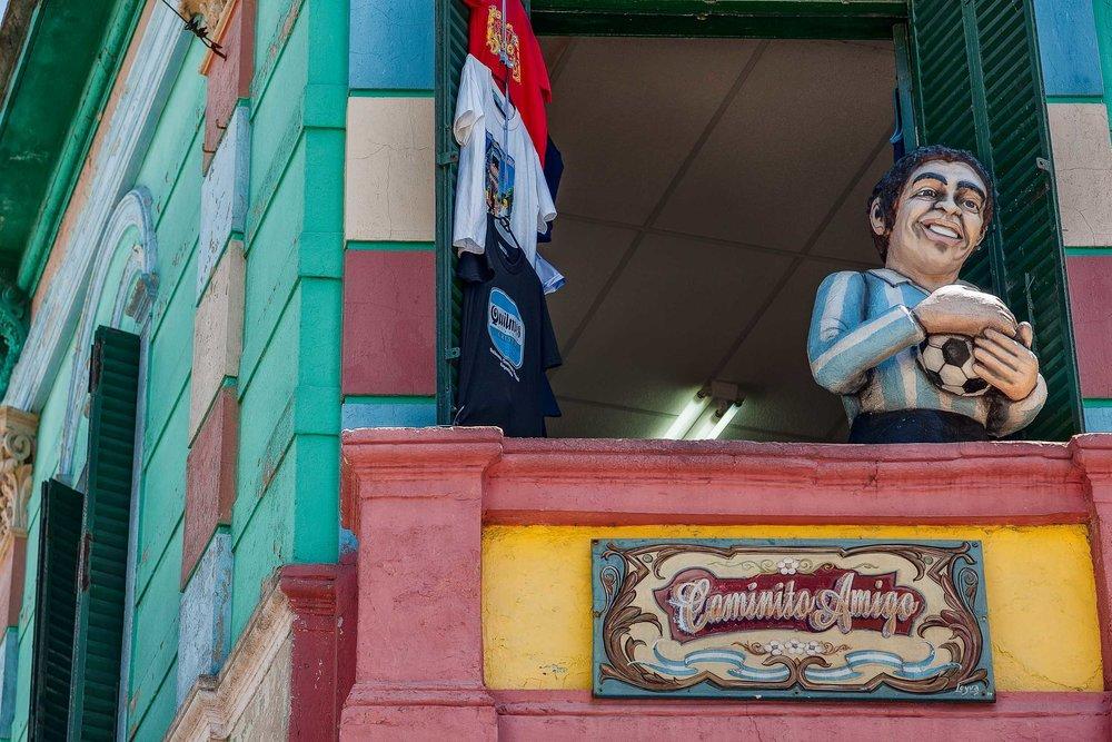 A    statue    of football legend    Diego Maradona    on a balcony in the    La Boca    precinct of    Buenos Aires, Argentina   .
