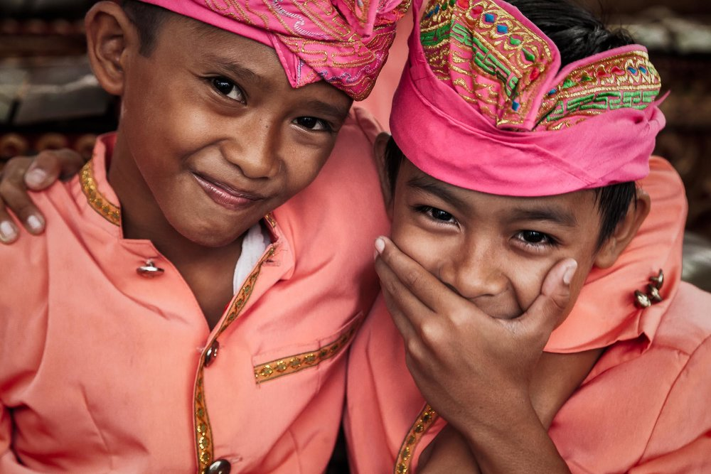 Two young boys   , very much enjoying a moment of mirth, at a local    band practice    near    Ubud, Bali   .