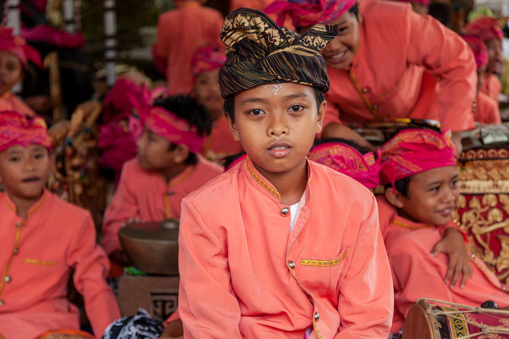 Portrait    of a    young boy   , in    local costume   , during a break at band practice near    Ubud, Bali   .