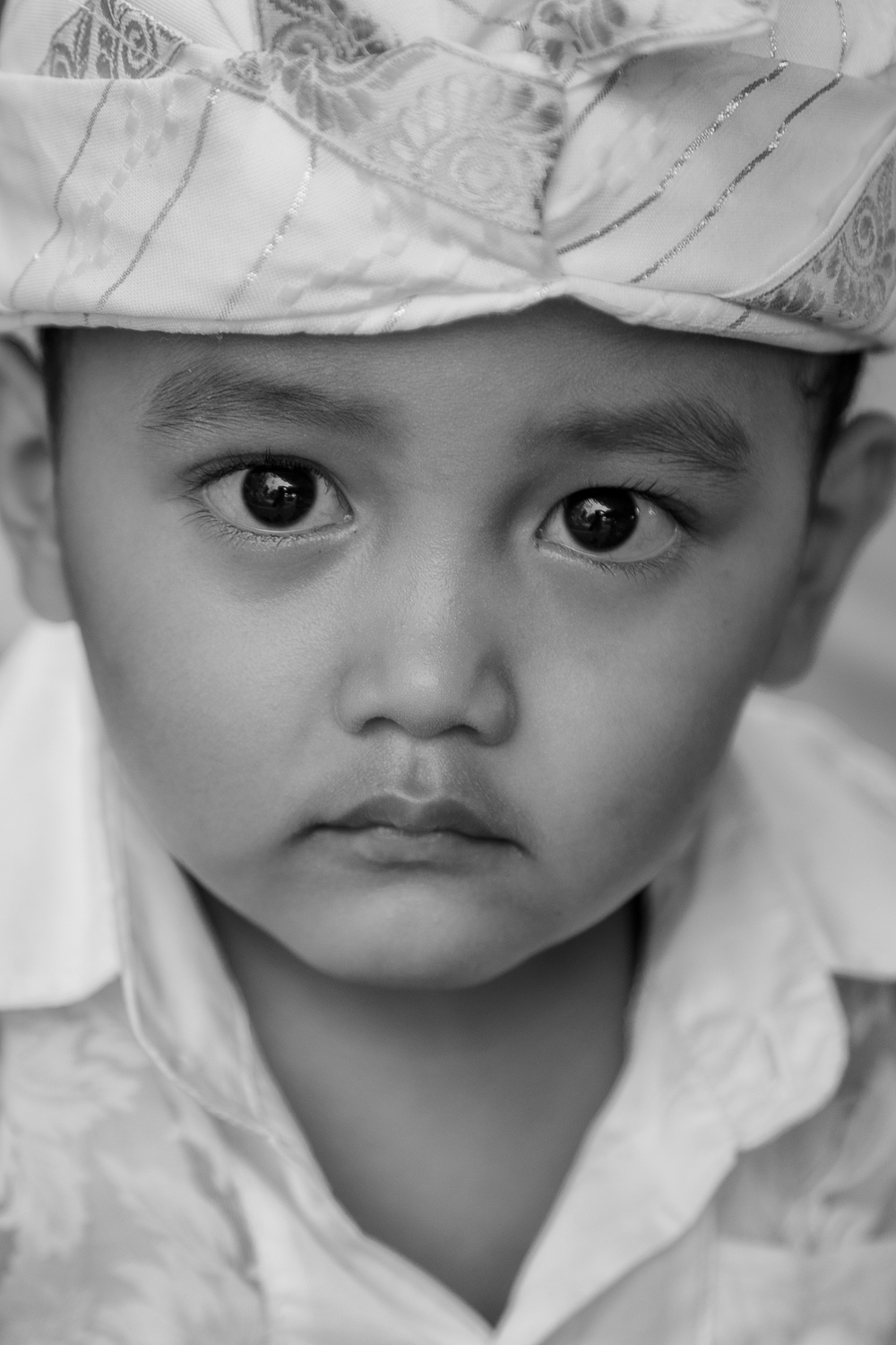 Black and white    portrait of a young boy    in a village near    Ubud, Bali   .