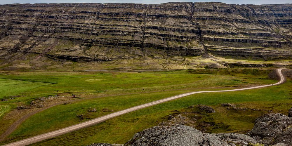 A dry,  dirt road  winds its way through  beautiful mountain scenerey  in rural  Iceland .