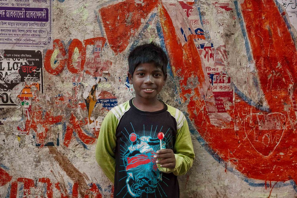 A  young boy  holding a  lollipop , that matches a similar looking item on his top, in  Kolkata, India .