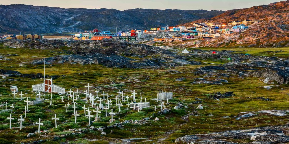 The  midnight sun  contrasts the  local cemetery  against a view of  houses and factories  in  Ilulissat, Greenland .