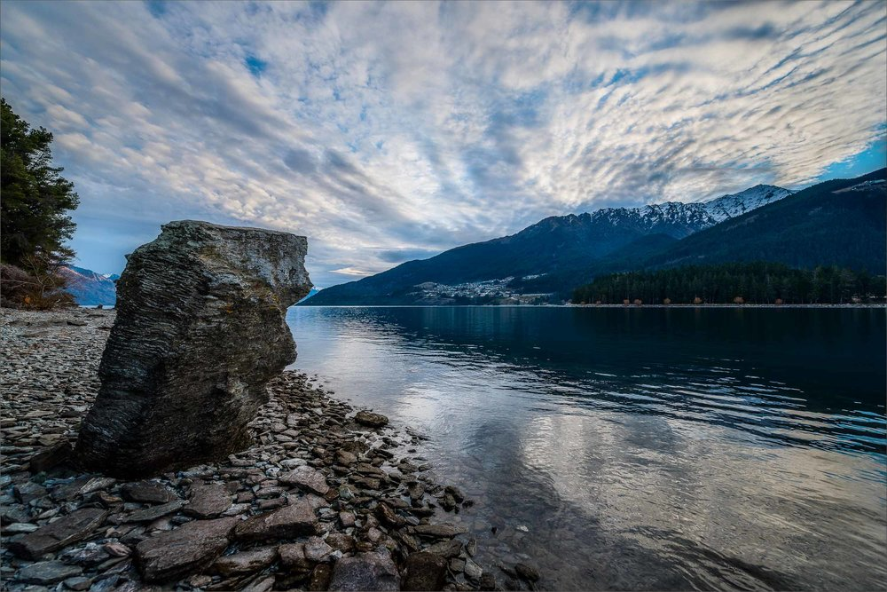 A large rock sits like a    silent sentinel    on the shore of    Lake Wakatipu    in    Queenstown, New Zealand   .