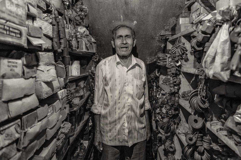 A man in his    spare parts store    in the backstreets of    Kolkata, India   .