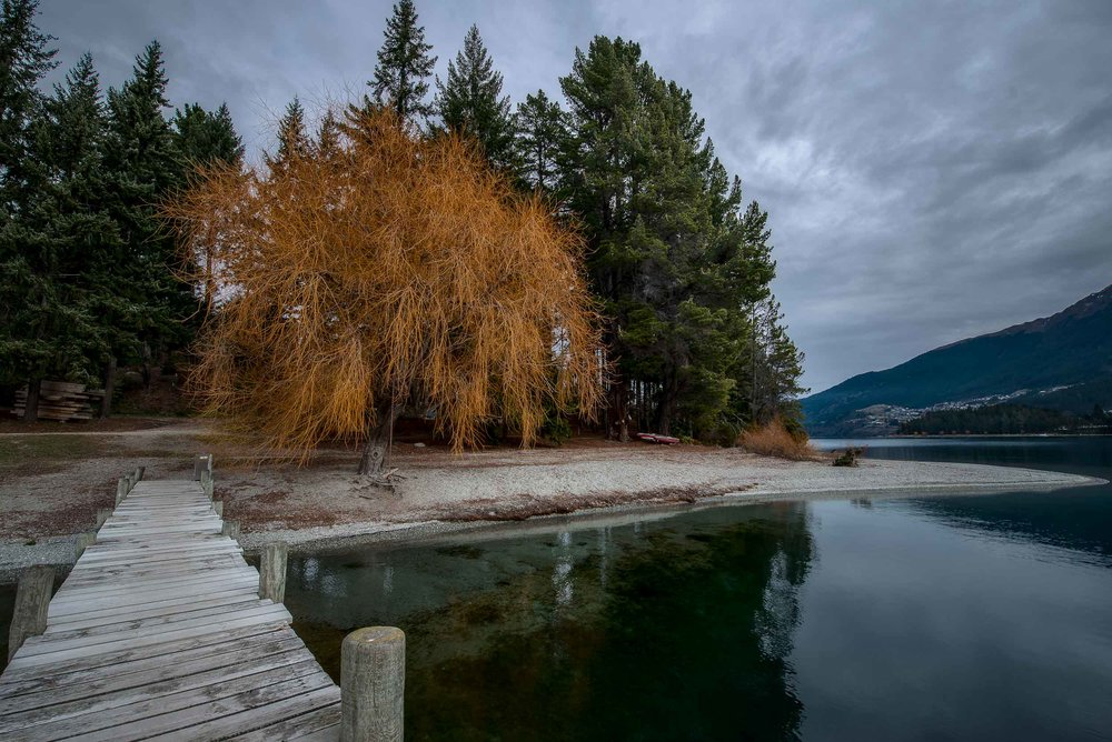 Looking back down a narrow pier towards    beautiful Autumn color    on    Lake Wakatipu   ,    Queenstown, New Zealand   .