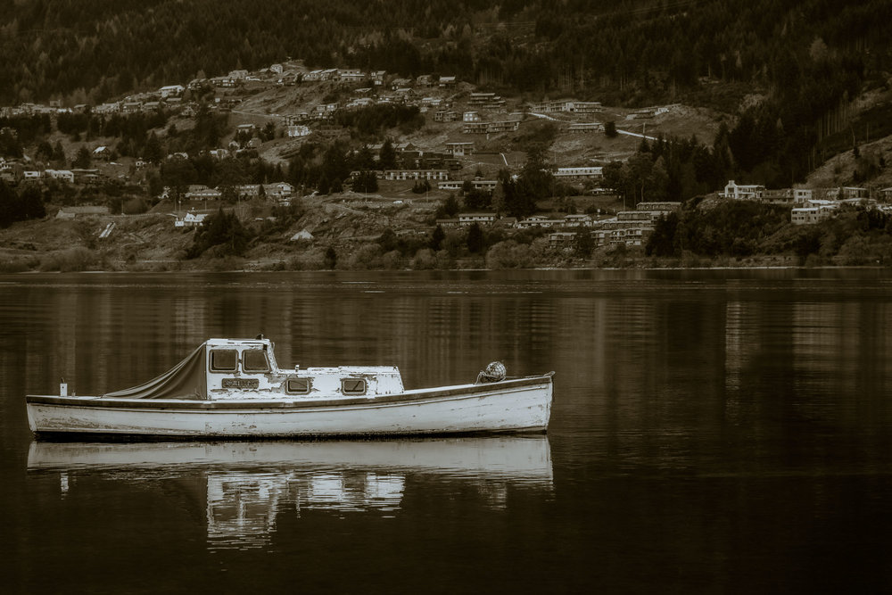 A    little boat    floats peacefully on    Lake Wakatipu    in    Queenstown, New Zealand   .