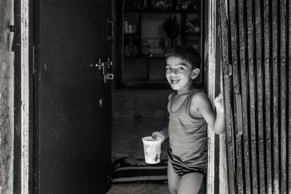 An    environmental portrait    of a    young boy    standing in the doorway of his home in the village of    Maria Purem    on the outskirts of    Chennai, India   .