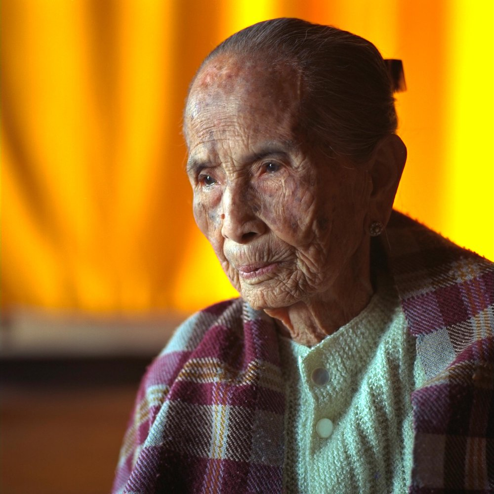 Portrait    of an    elderly woman    against    colorful curtains    in her home in rural    Myanmar   .
