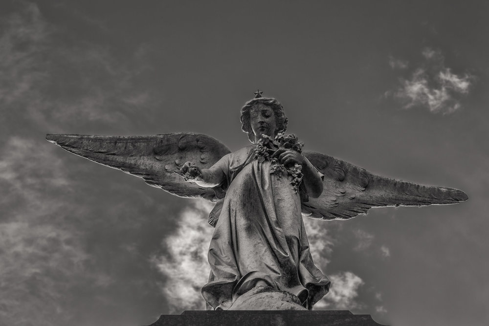 A dramatic black and white image of an    angel and sky    at    La Recoleta Cemetery   , Buenos Aires,    Argentina   .