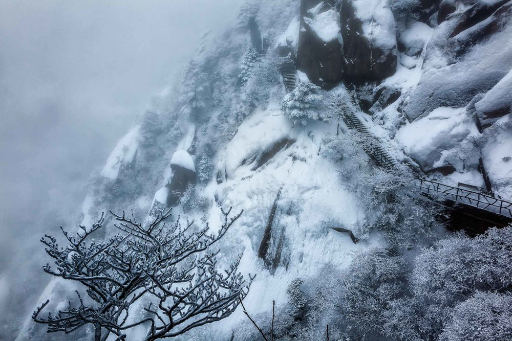 Deep snow    and    encroaching mist    almost hide a path, clinging to the side of the mountain, on    Huangshan    (i.e., Yellow Mountain) in    China    in the middle of winter.