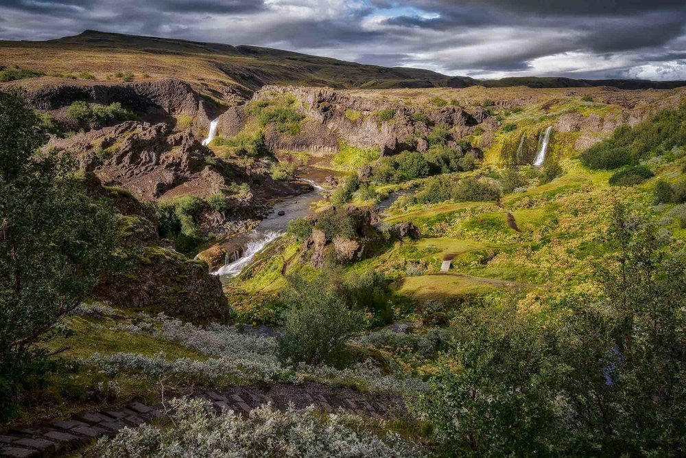 Twin waterfalls   , bathed in sunlight, feed a    fast flowing river    in the    Highlands    region of    Iceland   .