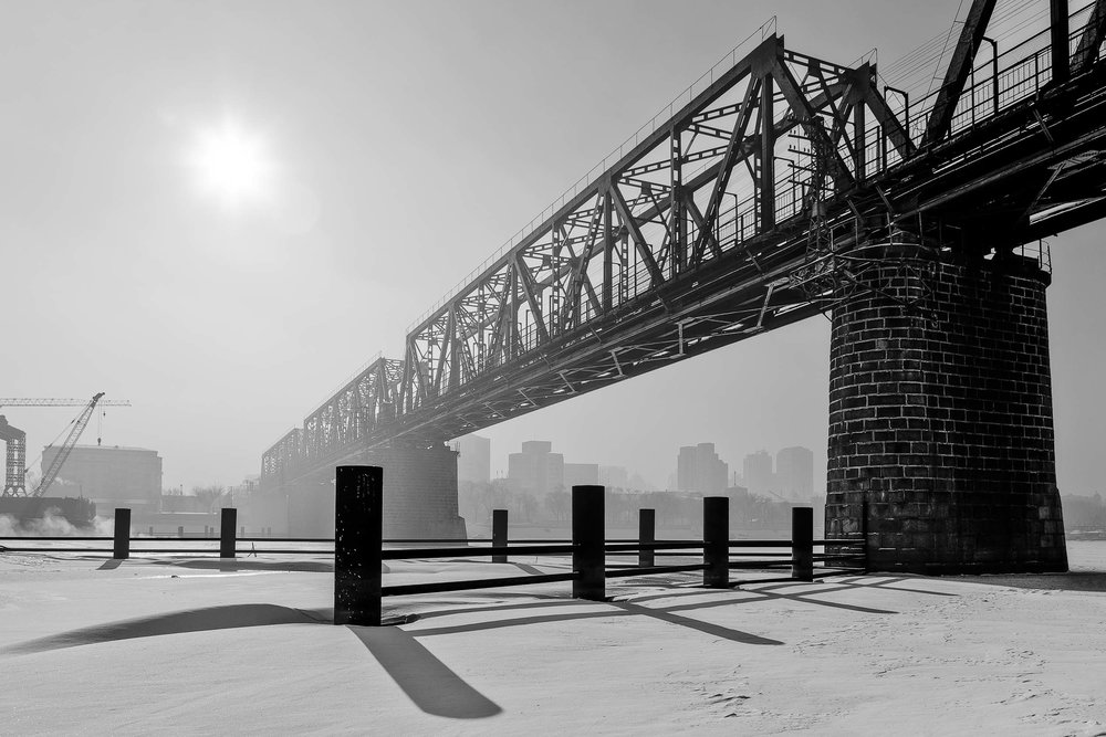 A    rail bridge   , in near silhouette, on an overcast winter's day in    Harbin, China   . The strong graphic shapes and shadows make for a dramatic image.