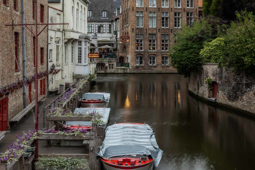 A lovely, restful photo of    boats    moored on the    canal    in the city of    Bruges, Belgium   .