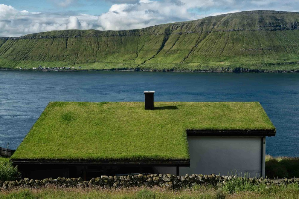 A lush    turf roof    on an idyllically located house by a fjord on the island of    Streymoy    in the    Faroe Islands   .