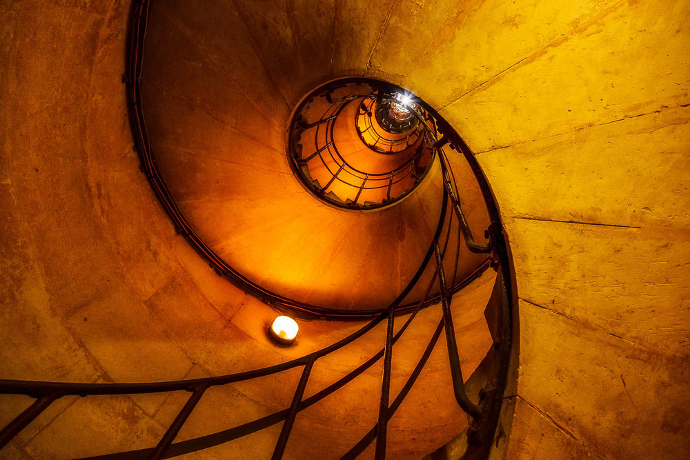A    worms eye viewpoint    provides a dramatic perspective of the    stairwell    that leads up to the top of the    Arc de Triomphe    in    Paris, France   .