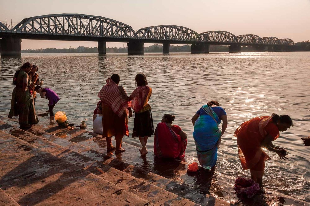 A group of visitors undertake    ritual bathing    by the banks of the    Hooghly River    in    Kolkata, India   .