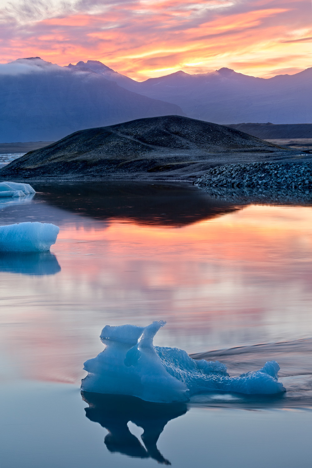 The serenity was palpable as the sun set on    Jökulsárlón Glacier Lagoon    in    Iceland   . The warmth of the sunset and the cool blue of the iceberg and lagoon provided a striking contrast in color and mood.