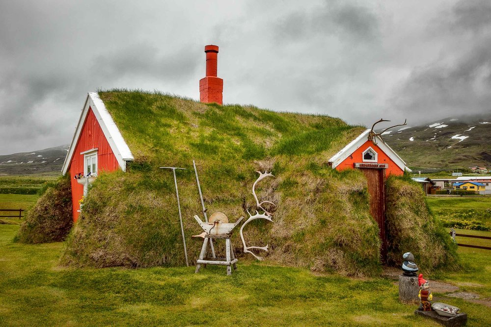 A colorful view of the famous    Lindarbakki turf house    in the village of    Bakkagerdi    in    Iceland   .