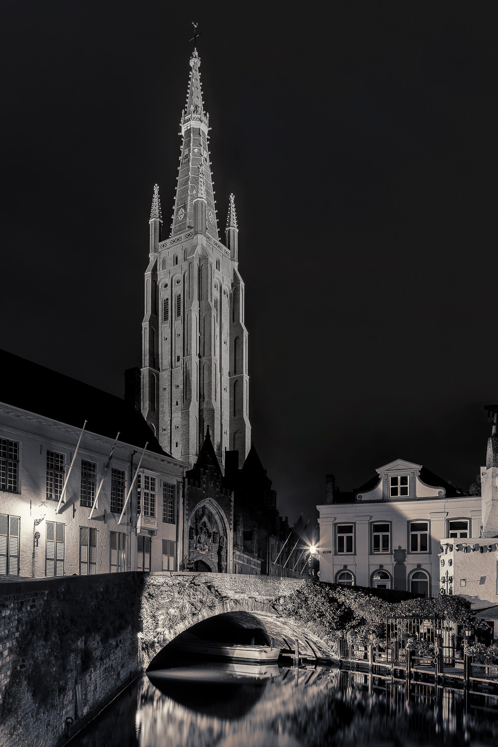 A peaceful scene depicting the    Church Of Our Lady   , under a dark night sky, in the city of    Bruges    (i.e., Brugge)    Belgium   .
