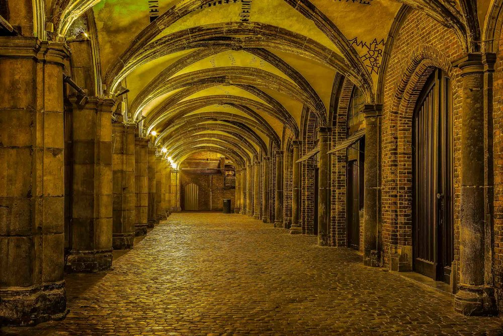 Artificial light    illuminates this    historical walkway    at night in the city of    Bruges    (i.e., Brugge),    Belgium   .
