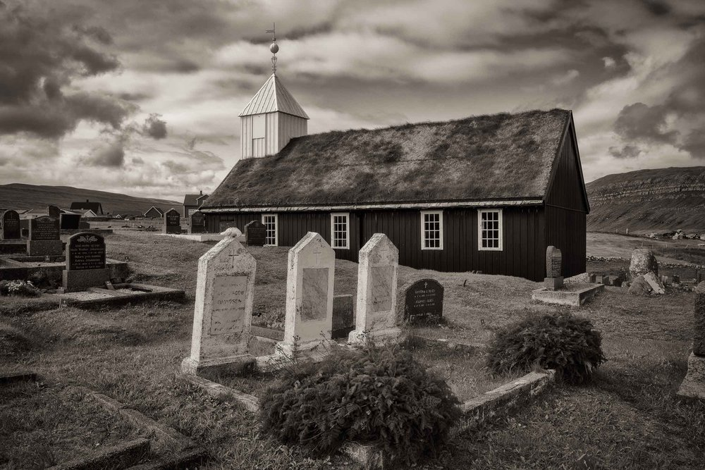 This lovely    wooden church    in the village of    Sandur   , on the island of Sandoy in the    Faroe Islands   , is a good example of traditional church architecture with    black tarred walls    topped by a    turf roof    and a    white belfry   .