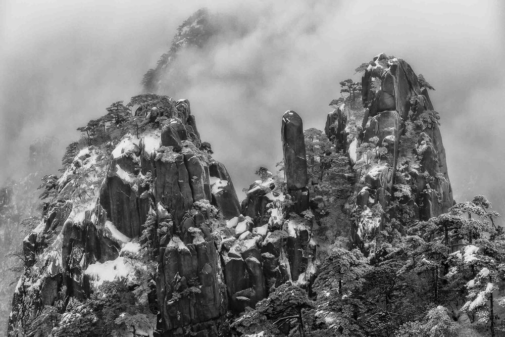 Mist recedes at a most serendipitous moment to reveal a    spectacular mountain view    on    Huangshan    (i.e., Yellow Mountain) in    China   .