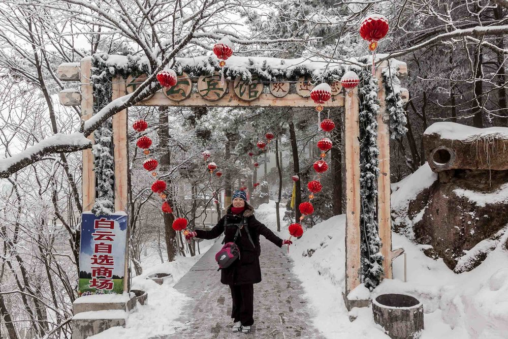 A    local tourist    poses for a photo near a hotel on    Huangshan    (i.e., Yellow Mountain) in    Eastern China   .