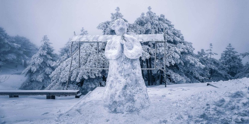A    snowman    greets visitors on    Huangshan    (i.e., Yellow Mountain) in    Eastern China   .