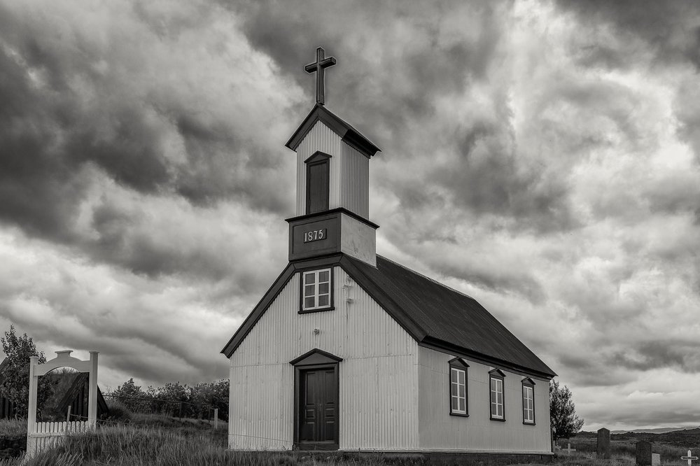 This    historic church    in    southern Iceland    is depicted against a dramatic sky foretelling a coming storm.