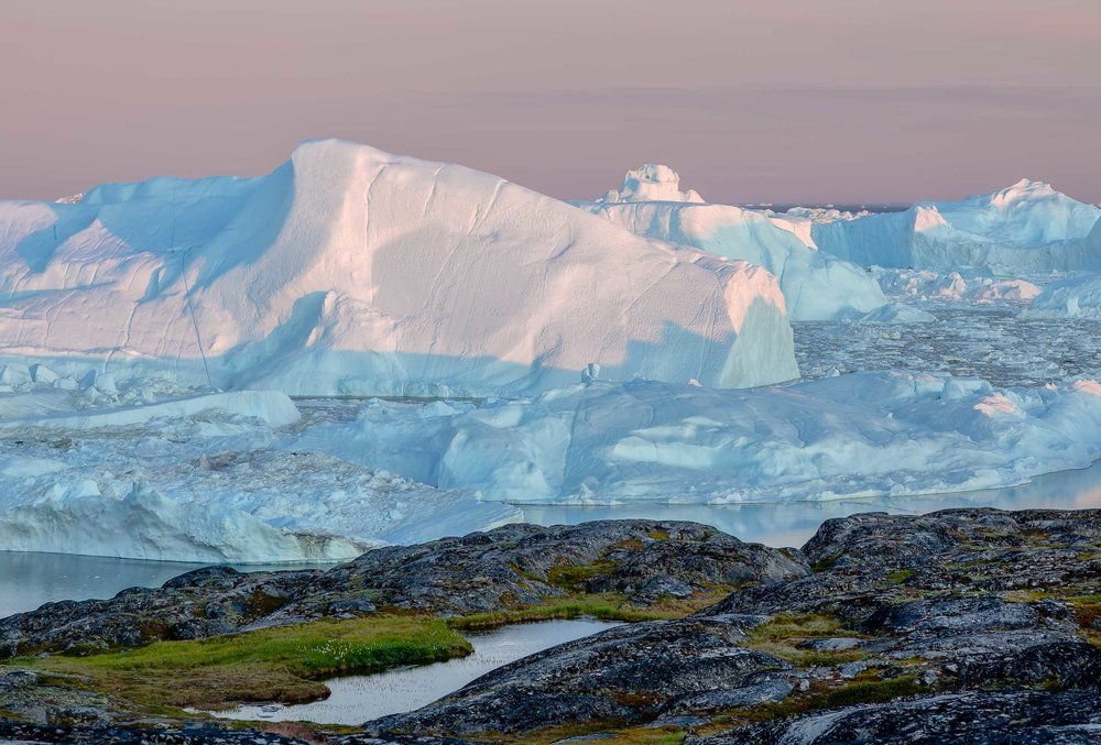 Delicate light illuminates a    gigantic iceberg    on the edge of the    Ilulissat Icefjord    in    Greenland   .