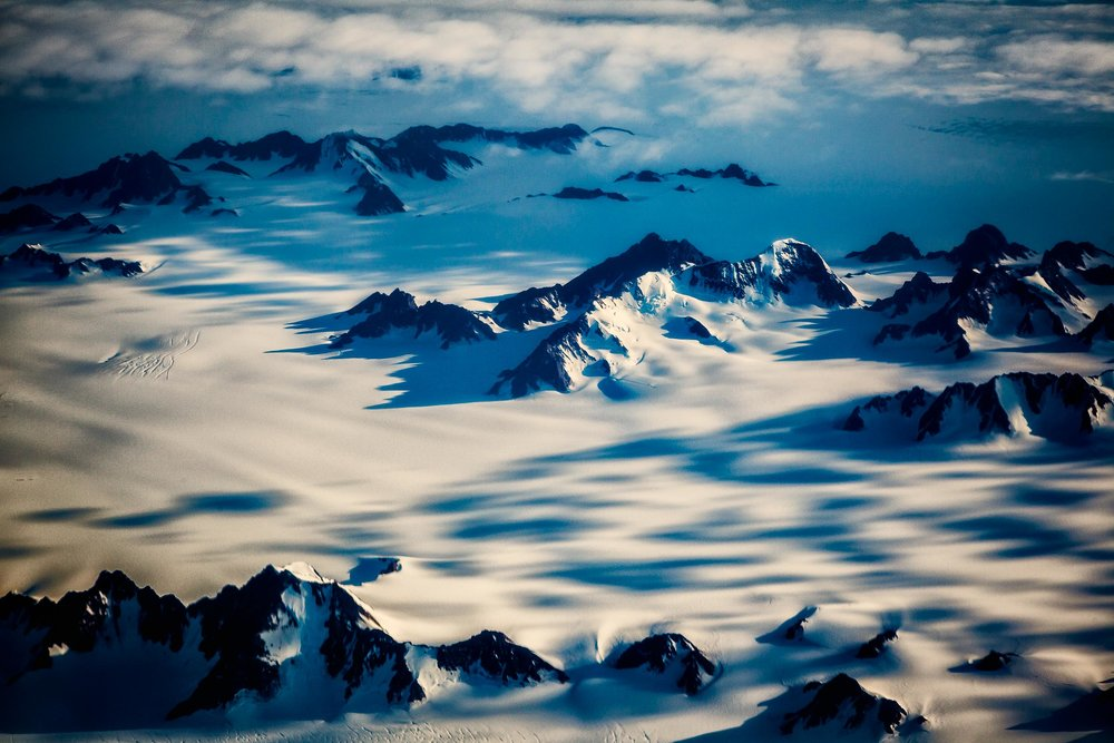 An    aerial view    of a    snow covered, mountainous landscape    made during a flight over    Greenland   .