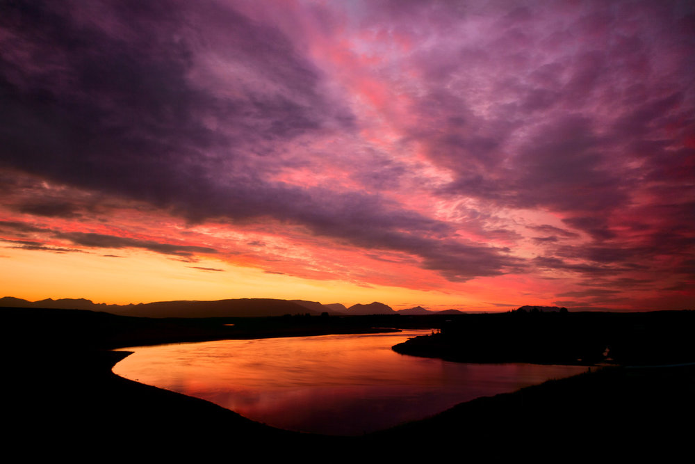 A    spectacular sunset   , after sinking just below the horizon, produces an    amazing afterglow    as it illuminates low lying clouds and a    small lake    on a farm in    southern Iceland   .