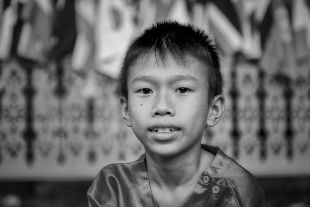 A    portrait    of a    young boy    at a cultural show, under low lighting conditions, in rural    Thailand   .