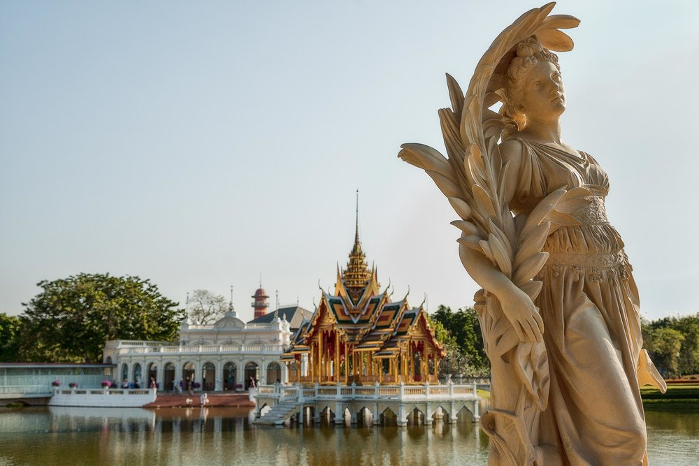 A graceful European    statue    in front of a classic thai-style pavillion at    Bang Pa In    near    Ayutthaya, Thailand   .